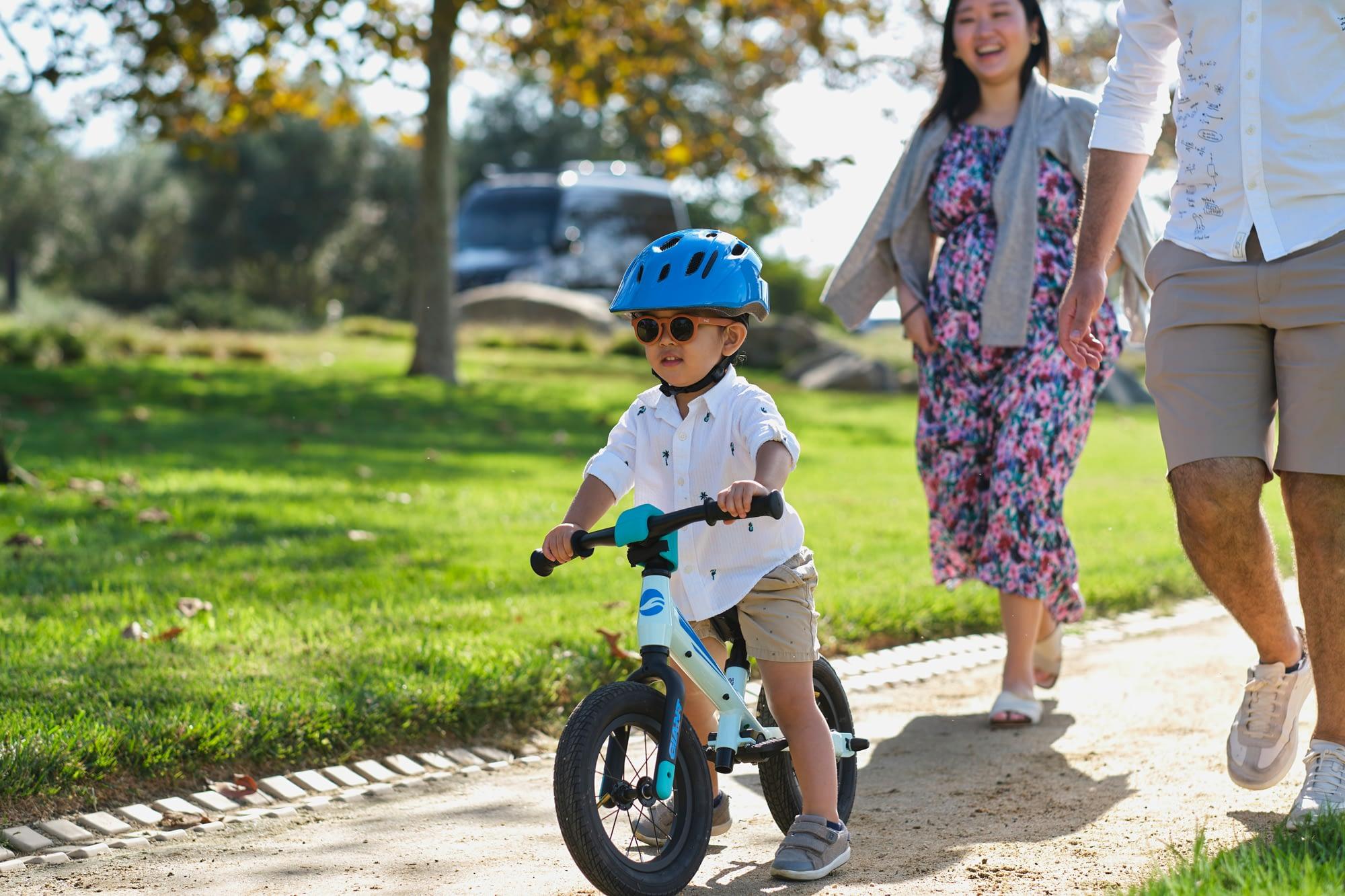 a little boy riding a kids bicycle