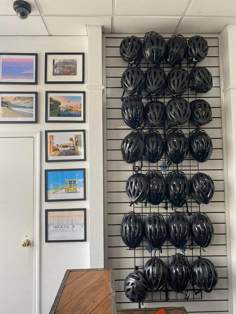 a wall of helmets hanging in a bike store