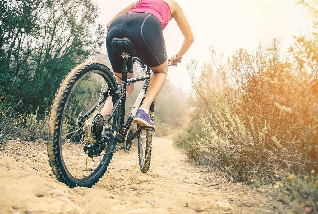 a biker wearing a pink top and black shorts rides a bike on a dusty path surrounded by shrubs