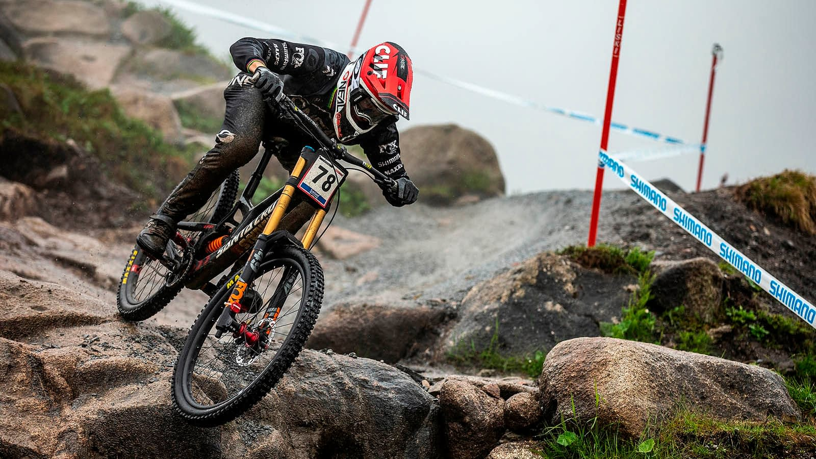 a biker in a red helmet going downhill on a yellow mountain bike