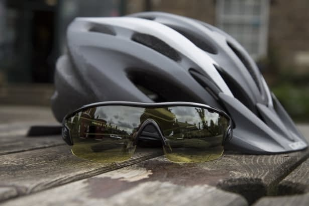 a pair of sunglasses next to a grey and white bike helmet on a wooden table