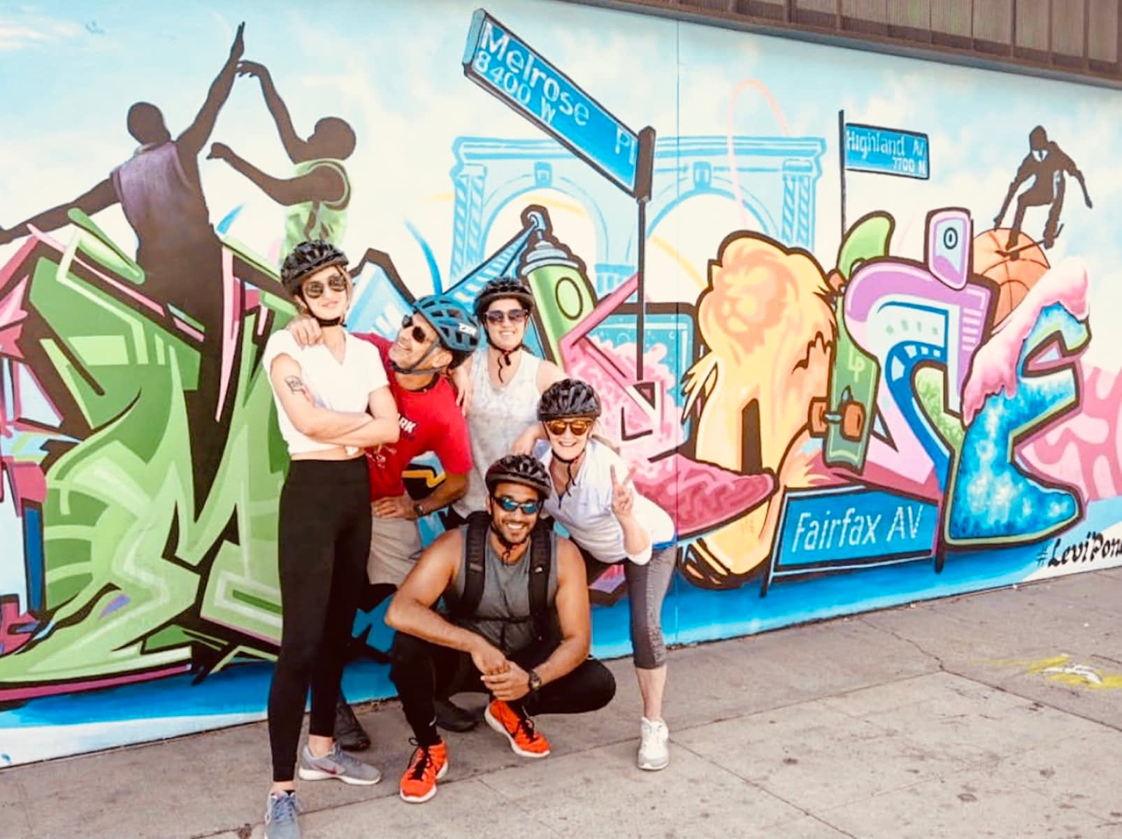 a photo of five people wearing sunglasses and bike helmets posing next to a mural of los angeles