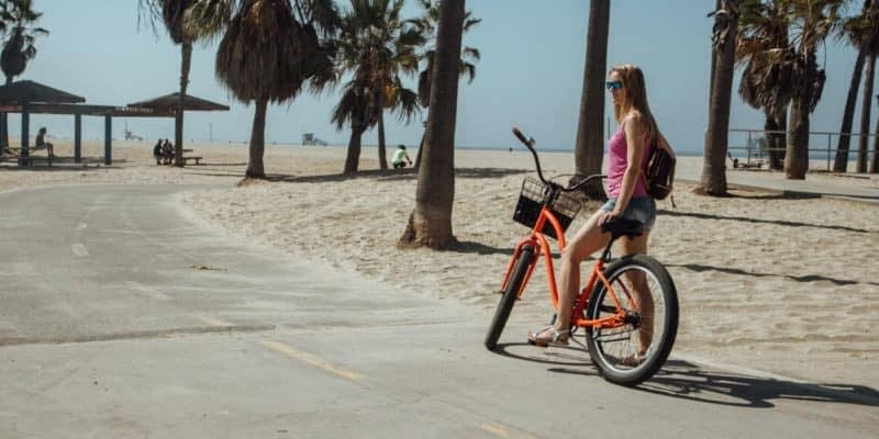 a woman riding an orange bike on a beach path near some palm trees
