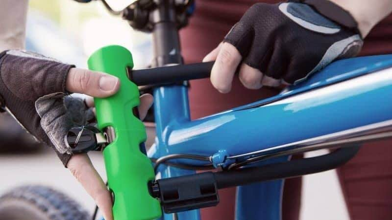 a close up of a person closing a green and black lock on a bright blue bicycle. the person is wearing black fingerless gloves.