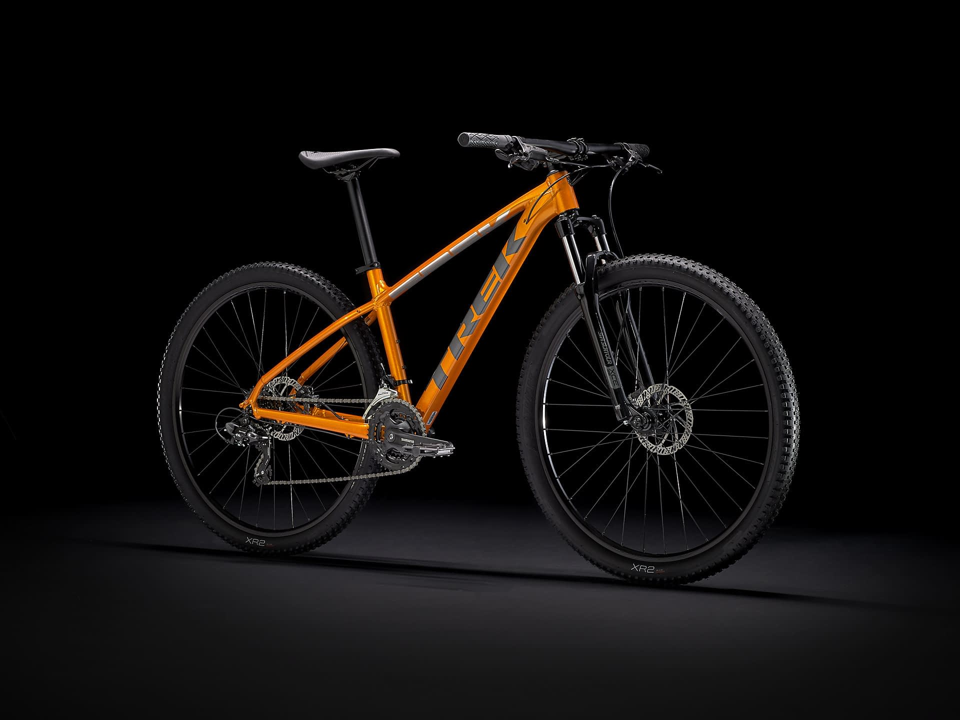 a mustard colored mountain bike with black tires on a black background