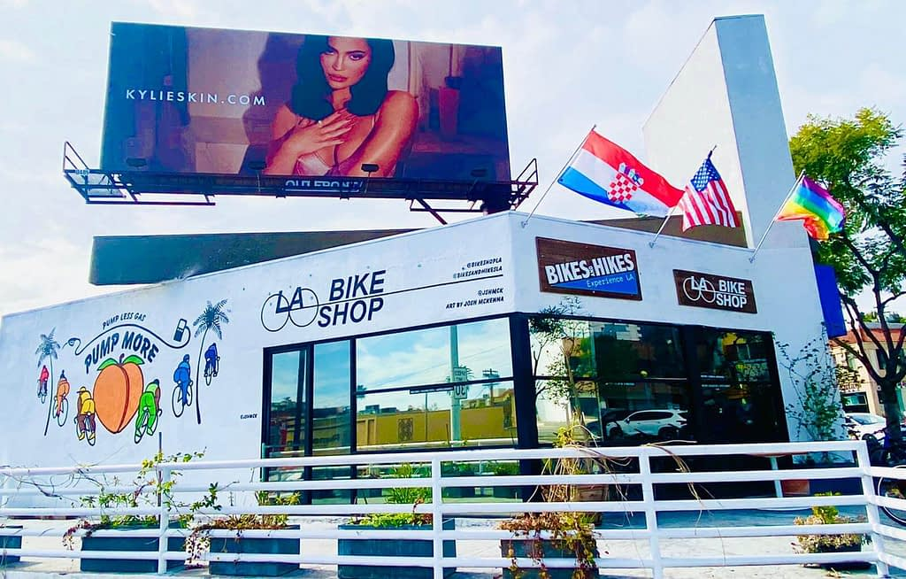 a bike shop in los angeles beneath a large billboard featuring an image of kylie jenner