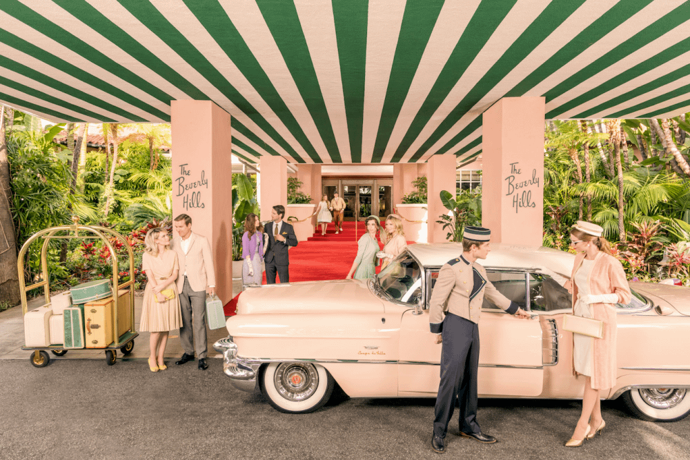 a pink car beneath a green and white striped awning at the beverly hills hotel