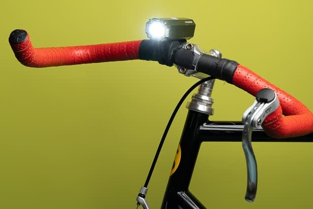 a close up of red bike handles on a black bicycle. there is an illuminated black bicycle light, and the photo has a chartreuse background.