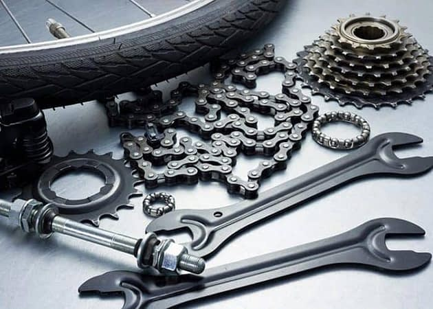 a bicycle tire, wrenches, gears, and a bike chain